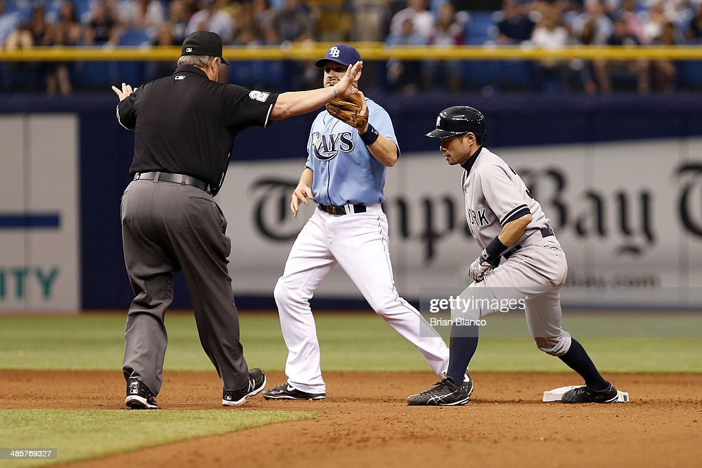 Umpire Marty Foster #60 calls safe on a decision that was later overturned by review as second baseman Logan Forsythe #10 of the Tampa Bay Rays catches Ichiro Suzuki #31 of the New York Yankees attempting to steal second base during the 11th inning of a game on April 20, 2014 at Tropicana Field in St. Petersburg, Florida.