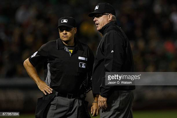 Umpire Paul Emmel talks to Mark Wegner during the eighth inning between the Oakland Athletics and the Toronto Blue Jays at the Oakland Coliseum on...