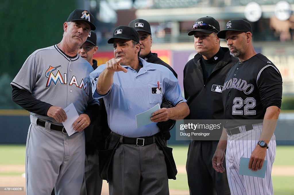 Umpire Phil Cuzzi reviews the ground rules with manager Dan Jennings #26 of the Miami Marlins and manager Walt Weiss #22 of the Colorado Rockies at Coors Field on June 5, 2015 in Denver, Colorado.