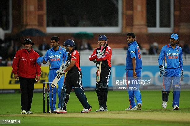 Umpire Richard Illingworth RP Singh of India Ravi Bopara of England Graeme Swann Munaf Patel and MS Dhoni look on before leaving the field after rain...