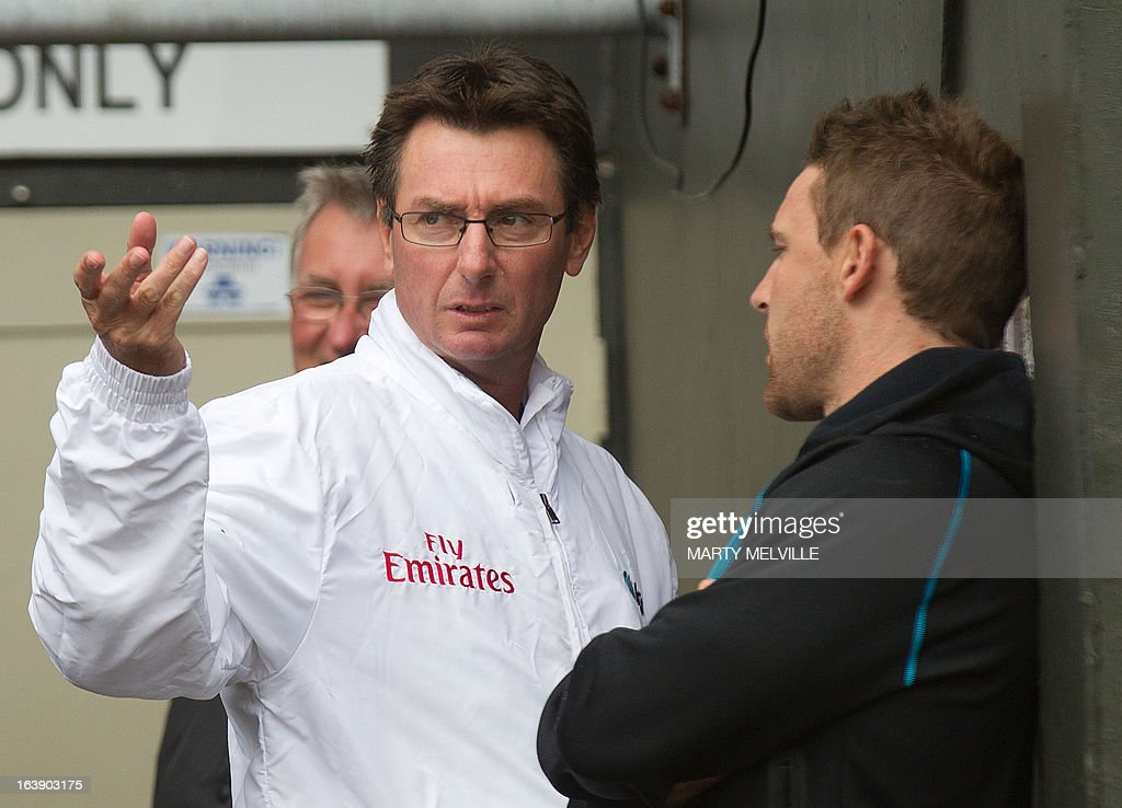 Umpire RJ Tucker of Australia talks to New Zealand team captain Brendon McCullum as rain halts play during day five of the international cricket Test match between New Zealand and England played at the Basin Reserve in Wellington on March 18, 2013. AFP PHOTO / Marty MELVILLE