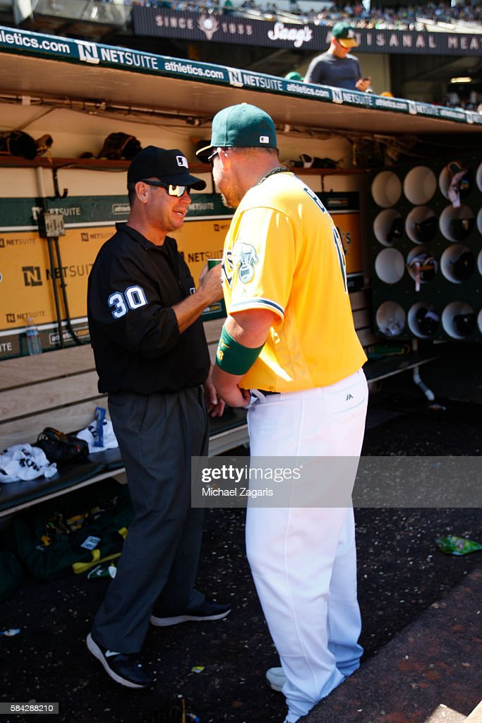 Umpire Rob Drake and Billy Butler of the Oakland Athletics stand in the dugout during the game against the Pittsburgh Pirates at the Oakland Coliseum...