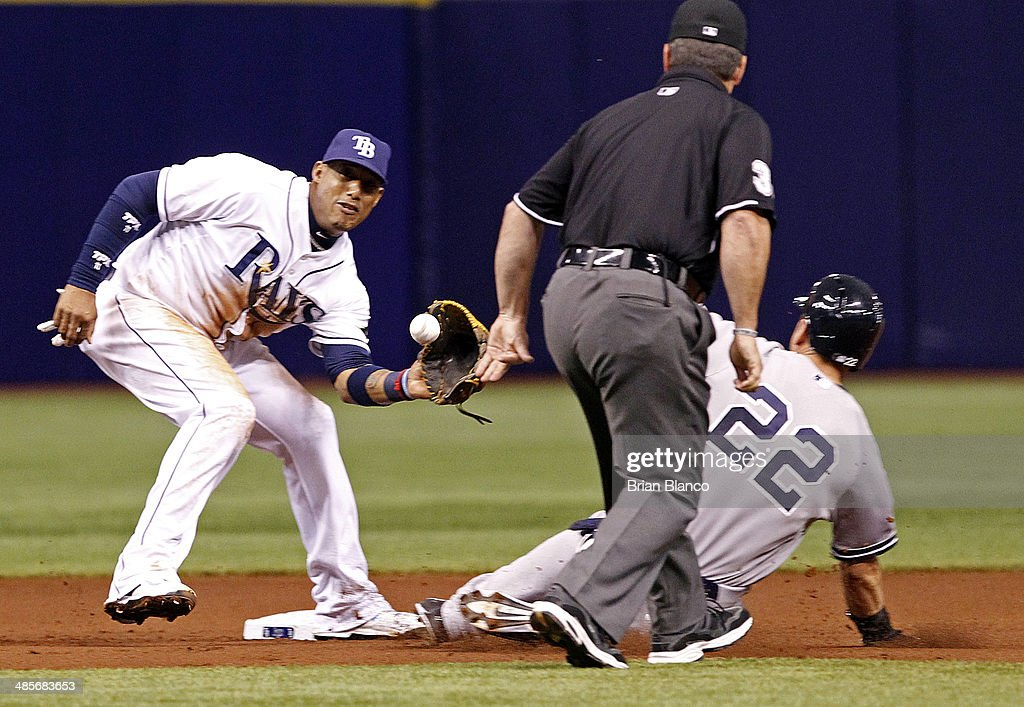 Umpire Rob Drake looks on as Shortstop Yunel Escobar of the Tampa Bay Rays catches Jacoby Ellsbury of the New York Yankees attempting to steal second...
