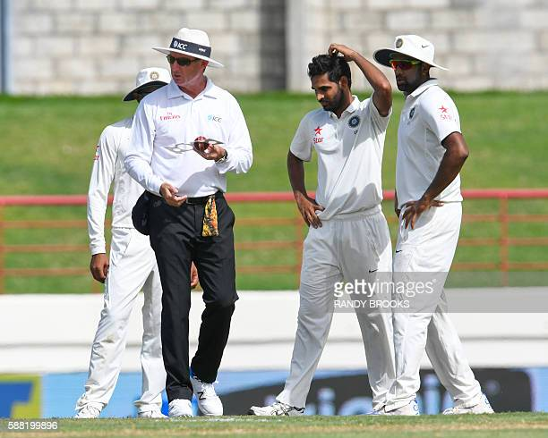 Umpire Rod Tucker checks the ball at the end of Bhuvneshwar Kumar of India over as Ravichandran Ashwin watch during day 2 of the 3rd Test between...