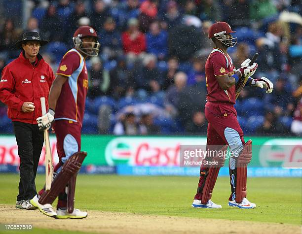 Umpire Rod Tucker looks on as Dwayne Bravo and Darren Sammy of West Indies have to accept that South Africa go through to the semifinal as the match...