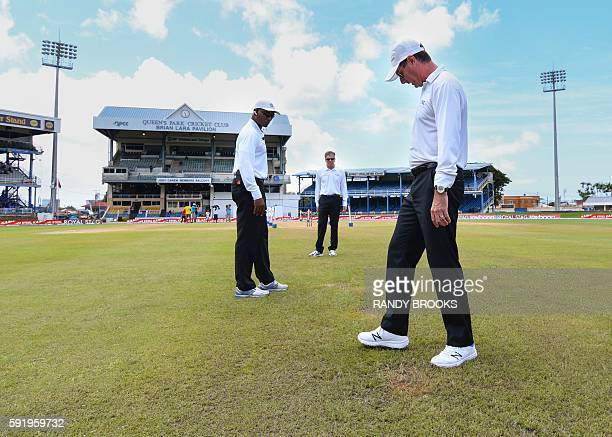 Umpire Rod Tucker Nigel Llong and Gregory Brathwaite inspect the pitch and out field during day 2 of the 4th and final Test between West Indies and...
