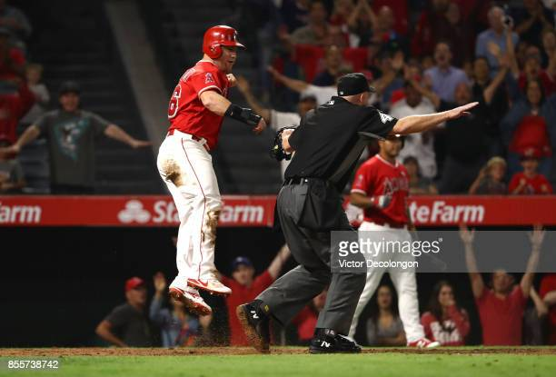 MLB umpire Ron Kulpa calls Kole Calhoun of the Los Angeles Angels of Anaheim safe at home after Calhoun scored on a tworun rbi double hit by teammate...