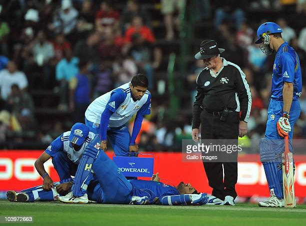 Umpire Rudi Koertzen watches over Harbhajan Singh who receives medical attention while lying injured on the pitch during the Airtel Champions League...