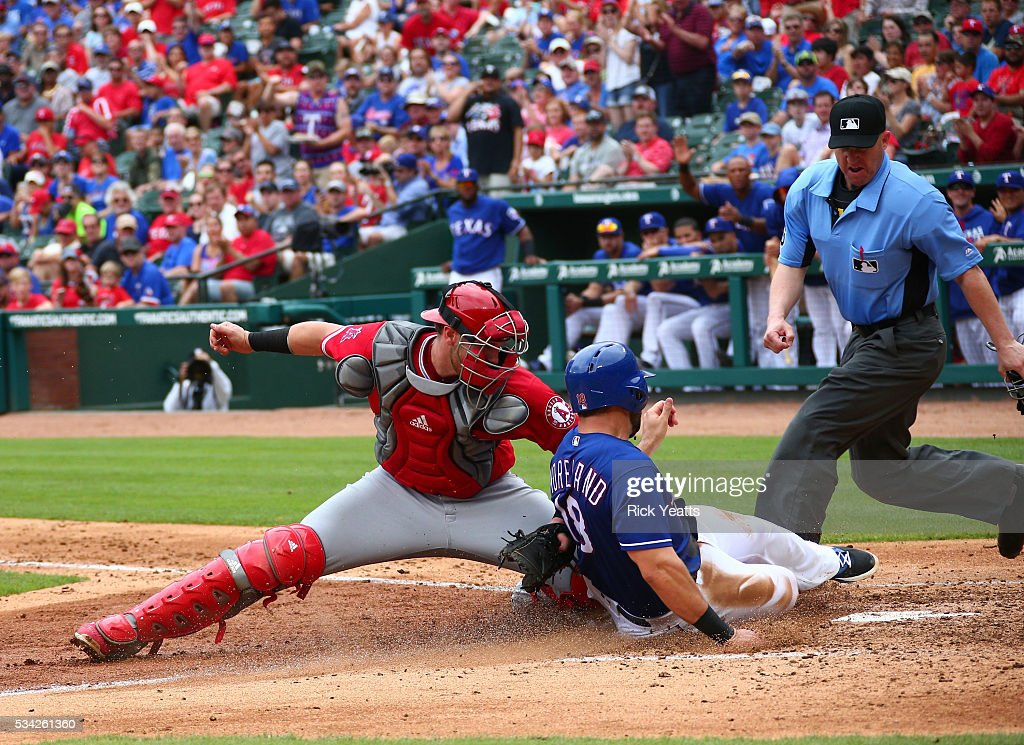 Umpire Ryan Blakney looks on as <a gi-track='captionPersonalityLinkClicked' href=/galleries/search?phrase=Mitch+Moreland&family=editorial&specificpeople=6824046 ng-click='$event.stopPropagation()'>Mitch Moreland</a> #18 of the Texas Rangers is tagged out by Jett Bandy #47 of the Los Angeles Angels of Anaheim in the third inning at Global Life Park in Arlington on May 25, 2016 in Arlington, Texas.