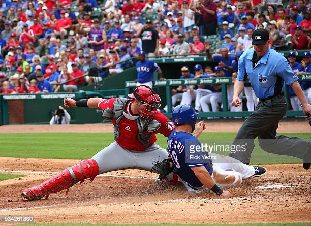 Umpire Ryan Blakney looks on as Mitch Moreland of the Texas Rangers is tagged out by Jett Bandy of the Los Angeles Angels of Anaheim in the third...
