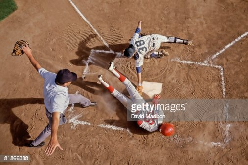 Umpire signaling baseball player safe as he slides into home plate with catcher attempting to tag him out.