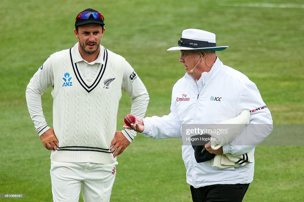 Umpire Steve Davis inspects a damaged ball while Hamish Rutherford of New Zealand looks on during day four of the Second Test match between New...