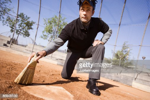 Umpire sweeping off home plate