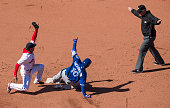 Umpire Ted Barrett signals Edwin Encarnacion of the Toronto Blue Jays safe after a tag attempt by Marco Hernandez of the Boston Red Sox in the...