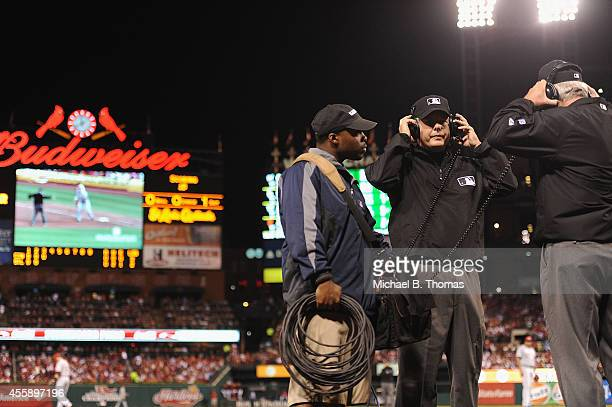 Umpire Tim Timmons reviews Instant Replay to determine Kolten Wong of the St Louis Cardinals was indeed out a first base in the third inning against...