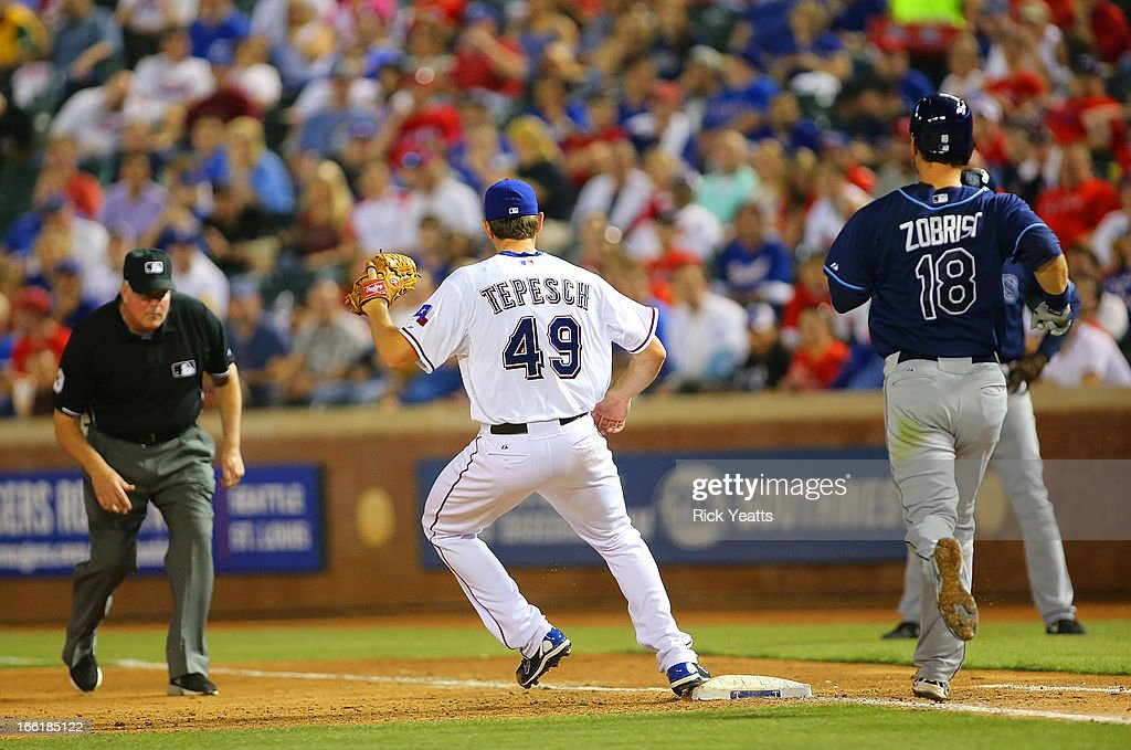 Umpire <a gi-track='captionPersonalityLinkClicked' href=/galleries/search?phrase=Tim+Welke&family=editorial&specificpeople=224714 ng-click='$event.stopPropagation()'>Tim Welke</a> #3 looks on as Nick Tepesch #49 of the Texas Rangers makes the out on <a gi-track='captionPersonalityLinkClicked' href=/galleries/search?phrase=Ben+Zobrist&family=editorial&specificpeople=2120037 ng-click='$event.stopPropagation()'>Ben Zobrist</a> #18 of the Tampa Bay Rays on first base at Rangers Ballpark in Arlington on April 9, 2013 in Arlington, Texas.