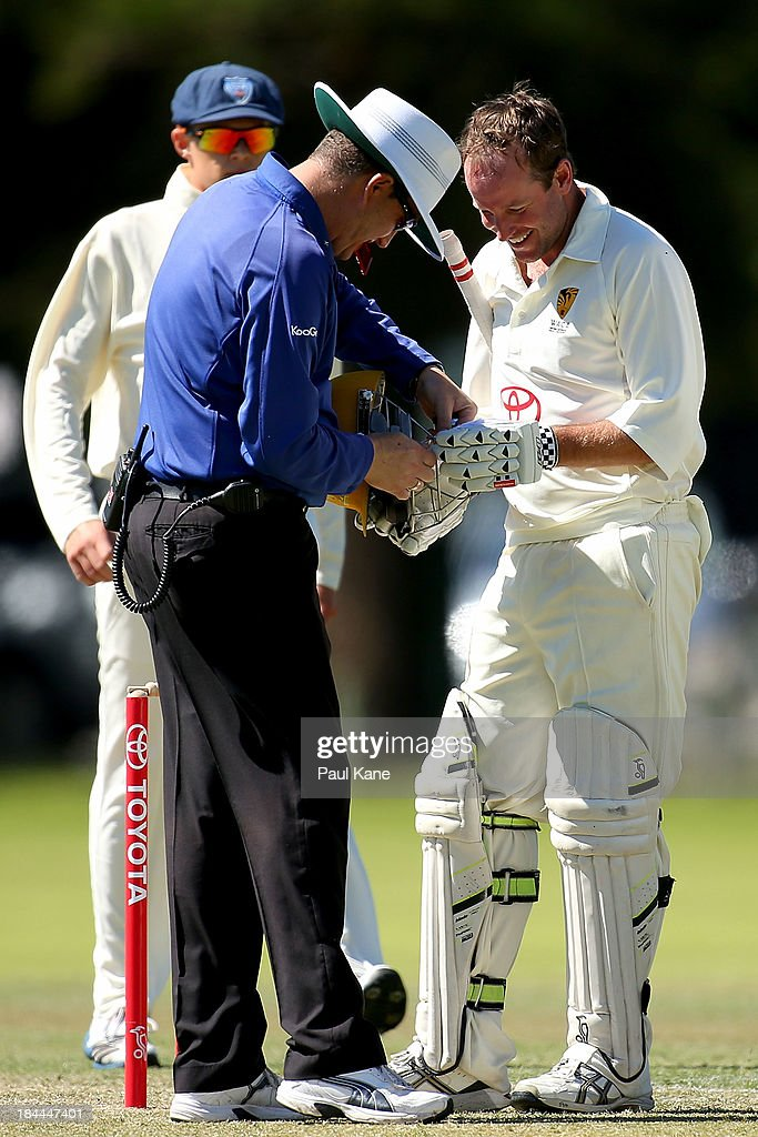 Umpire Todd Rann adjusts the helmet strap for James Boyland of Western Australia during day one of the Futures League match between Western Australia and New South Wales at Richardson Park on October 14, 2013 in Perth, Australia.