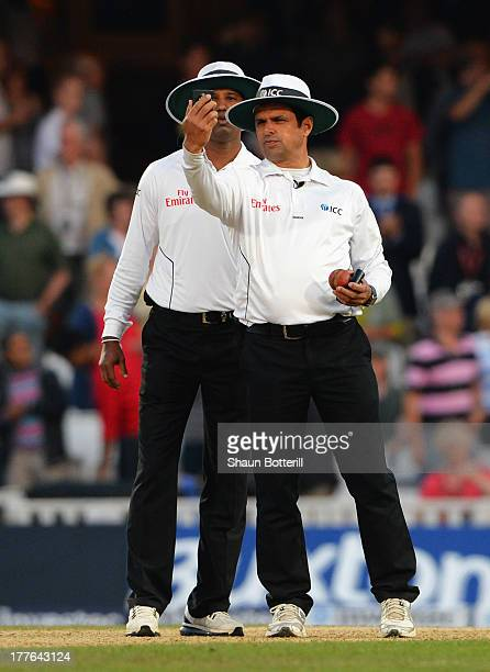 Umpires Aleem Dar and Kumar Dharmasena take a light reading during day five of the 5th Investec Ashes Test match between England and Australia at the...