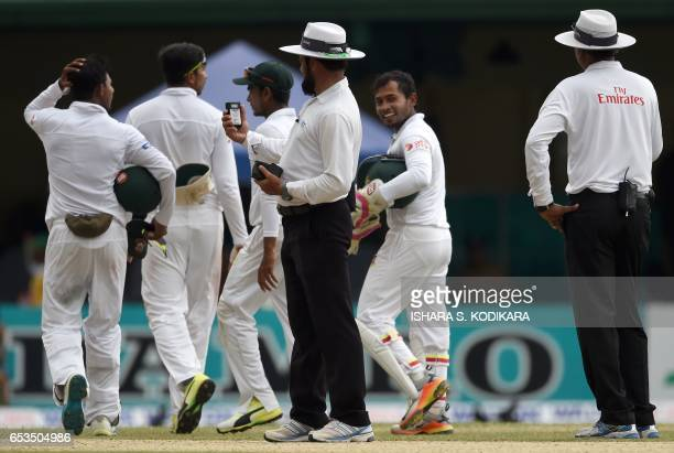 Umpires Aleem Dar and S Ravi take an ambient light reading watched by Bangladeshi players during the first day of the second and final Test cricket...