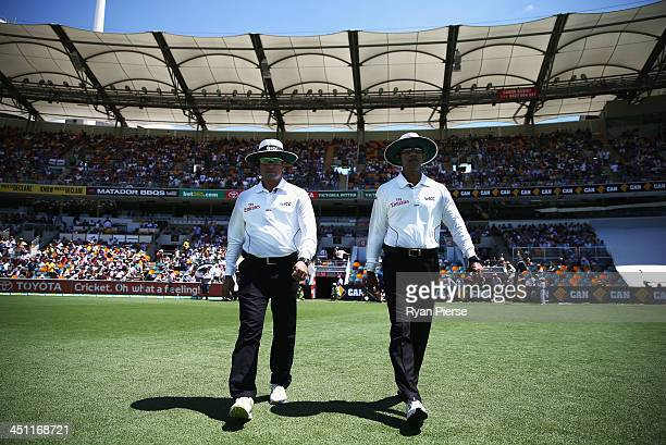 Umpires Aleem Dar and Umpire Kumar Dharmasena walk out onto the ground during day two of the First Ashes Test match between Australia and England at...