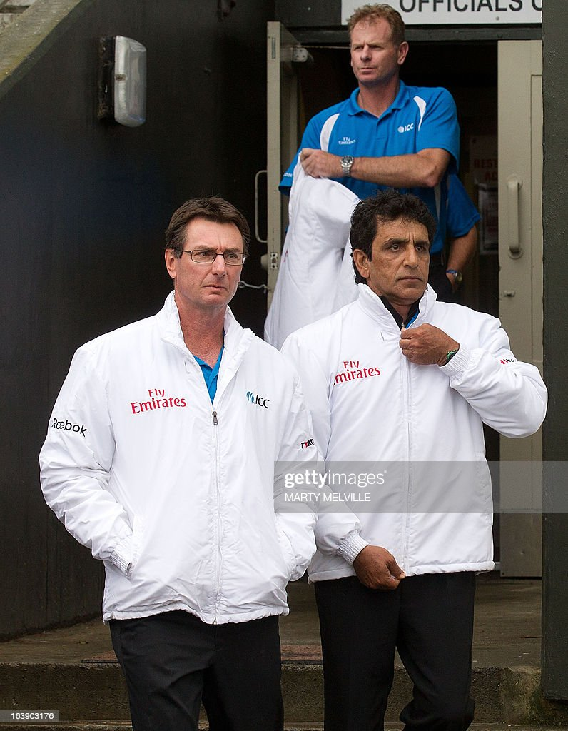 Umpires Asad Rauf (lower R) of Pakistan, RJ Tucker of Australia (lower L) and TV umpire PR Reiffel of Australia (rear) walk out to check the pitch as rain halts play during day five of the international cricket Test match between New Zealand and England played at the Basin Reserve in Wellington on March 18, 2013. AFP PHOTO / Marty MELVILLE