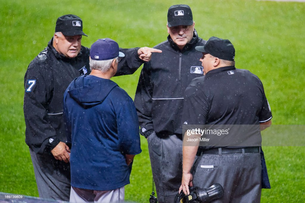 Umpires <a gi-track='captionPersonalityLinkClicked' href=/galleries/search?phrase=Brian+O%27Nora&family=editorial&specificpeople=545809 ng-click='$event.stopPropagation()'>Brian O'Nora</a> #7 Bill Welke #52 and Fieldin Culbreth #25 talk with <a gi-track='captionPersonalityLinkClicked' href=/galleries/search?phrase=Joe+Maddon&family=editorial&specificpeople=568433 ng-click='$event.stopPropagation()'>Joe Maddon</a> #70 of the Tampa Bay Rays about the weather during the second inning against the Cleveland Indians at Progressive Field on May 31, 2013 in Cleveland, Ohio.