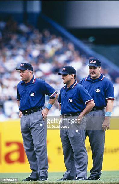Umpires Brian O'Nora Mark Hirschbeck and Wally Bell look on during the New York Yankees game against the Chicago White Sox at Yankee Stadium on June...