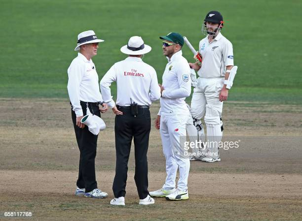 Umpires Bruce Oxenford and Rod Tucker discuss the state of the ball with Captain Faf du Plessis of South Africa watched on by Captain Kane Williamson...