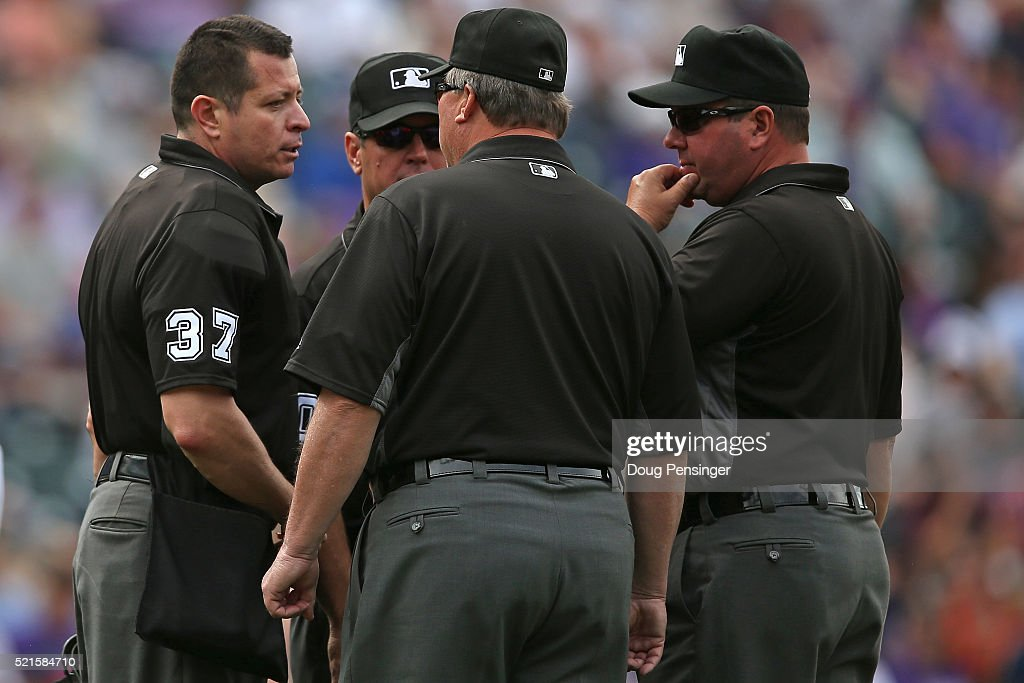 Umpires Carlos Torres Rob Drake Gerry Davis and Sam Holbrook confer about a call as the San Francisco Giants face the Colorado Rockies at Coors Field...