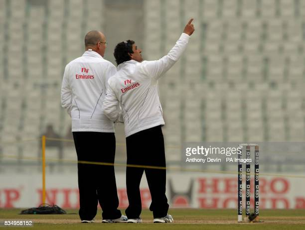 Umpires Daryl Harper and Asad Rauf check the light as fog delays the start of play before the fourth day of the second test at the Punjab Cricket...