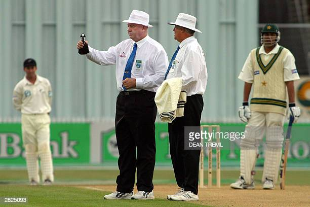 Umpires David Orchard and Steve Davis check the light before suspending play due the darkness while Pakistan captain Inzamam Ul Haq and New Zealand...