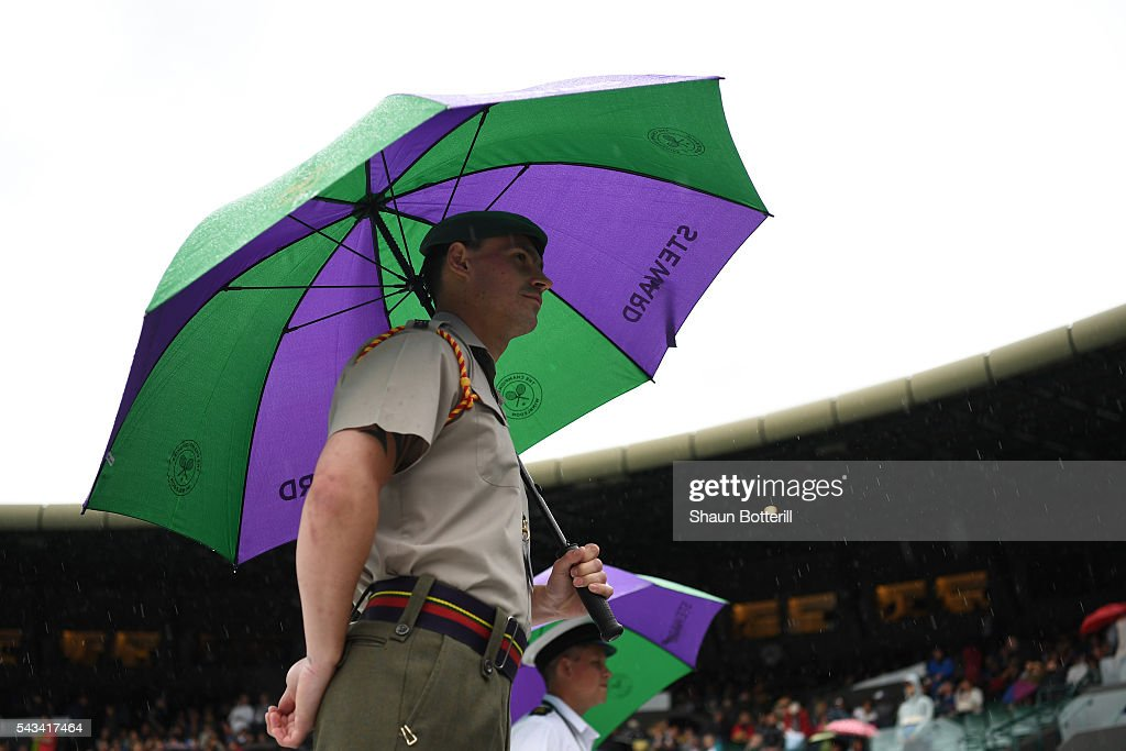 Umpires hide undernieth umbrellas on court one, during day two of the Wimbledon Lawn Tennis Championships at the All England Lawn Tennis and Croquet Club on June 28, 2016 in London, England.