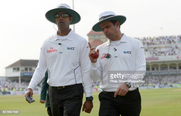 Umpires Kumar Dharmasena and Aleem Dar leave the field after the third day's play during the 1st Test match between England and Australia at Trent...