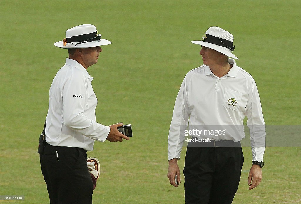 Umpires Mick Martell and Damien Mealey discuss bad light on a rain interupted day during day one of the Sheffield Shield match between the New South Wales Blues and the Queensland Bulls at Sydney Cricket Ground on November 22, 2013 in Sydney, Australia.