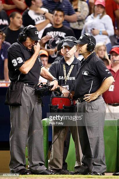 Umpires Mike Winters and Mark Wegner review a call during the eighth inning of the game between the Miami Marlins and the Cincinnati Reds at Marlins...