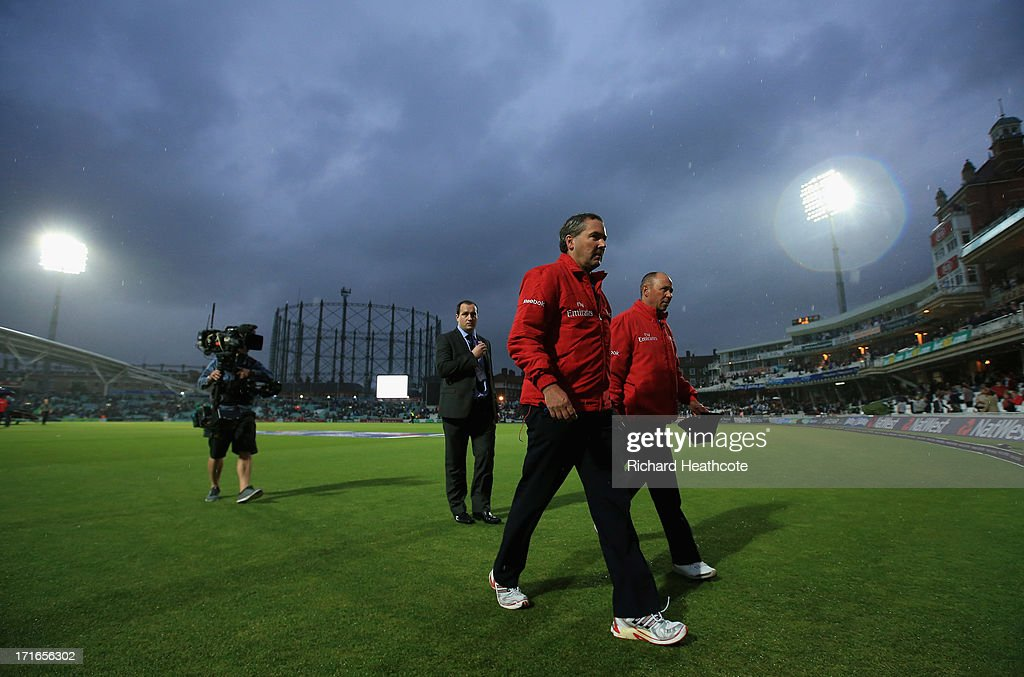 Umpires Richard Illingworth and Tim Robinson walk off the pitch as the game is abandoned during the 2nd Natwest International T20 match between England and New Zealand at The Kia Oval on June 27, 2013 in London, England.