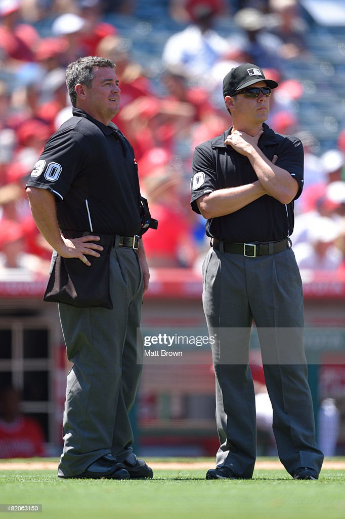 Umpires Rob Drake and DJ Reyburn wait as a tag play is reviewed during the ninth inning of the game between the Minnesota Twins and the Los Angeles...