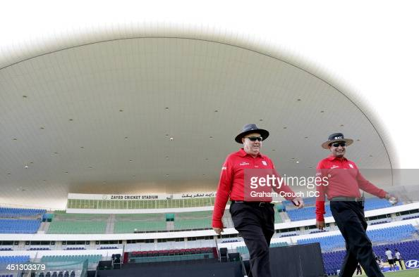 Umpires Steve Davis and Shozab Raza walk on the pitch ahead of the Canada v UAE match at the ICC World Twenty20 Qualifiers at the Zayed Cricket...