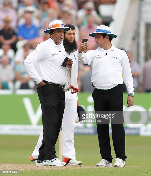 Umpires Sundaram Ravi and Aleem Dar consult a light meter during day two of the 4th Investec Ashes Test match between England and Australia at Trent...