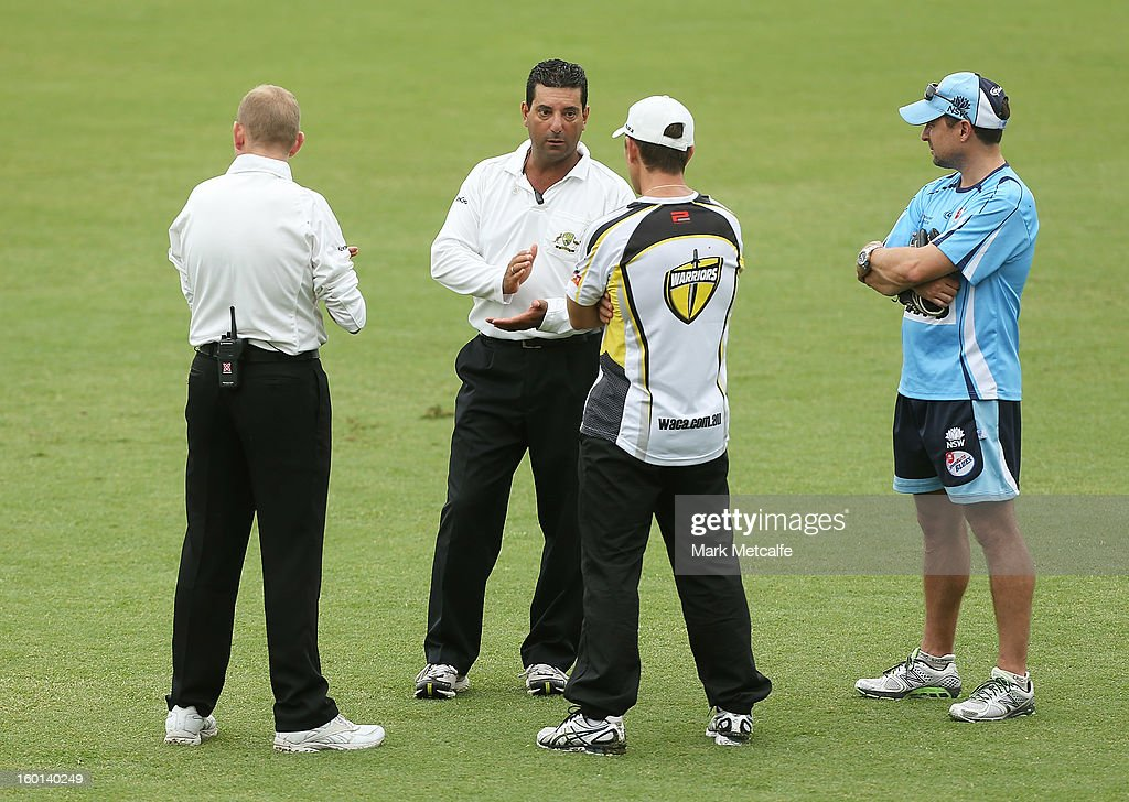 Umpires talk to coaching staff from the Blues and the Warriors as rain delays the start of day four of the Sheffield Shield match between the New South Wales Blues and the Western Australia Warriors at Bankstown Oval on January 27, 2013 in Sydney, Australia.