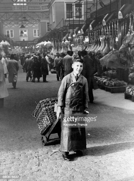 Un adolescent garçonboucher tire une charrette dans une halle à viande