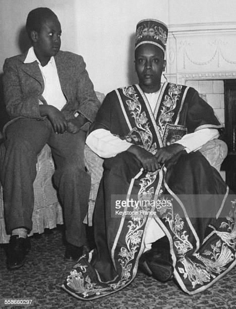 Un chef d'une tribu ougandaise en habits traditionnels en compagnie de son fils est invité à la cérémonie du Couronnement de la Reine Elizabeth le 16...