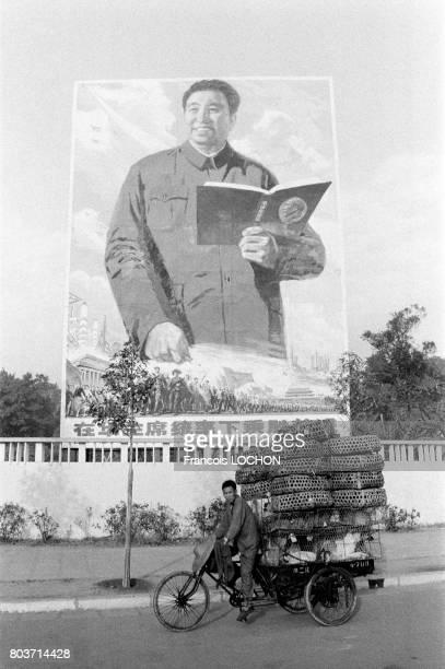 Un chinois transporte des marchandises sur son vélo sous l'effigie de Hua Guofengen à Canton en décembre 1977 en Chine