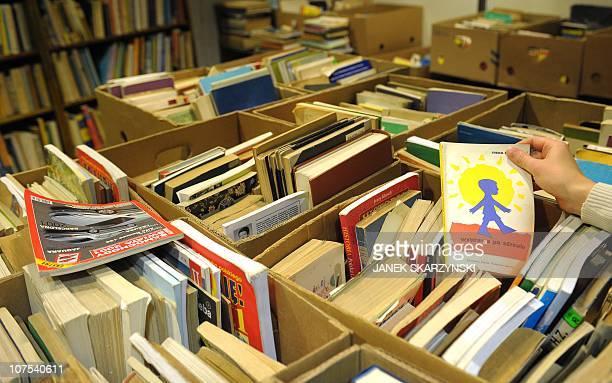 Un 'Cimetière des livres oubliés' pour les ressusciter à VarsovieA visitor peruses books on offer at Warsaw's 'Cemetery of Forgotten Books' set up by...