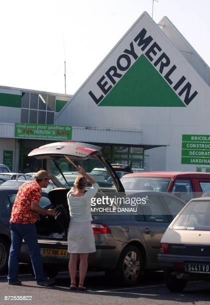 Un couple charge le coffre de leur voiture avec leurs achats effectués au magasin Leroy Merlin de Mondeville le 10 août 2004 Leroy Merlin détient 31%...