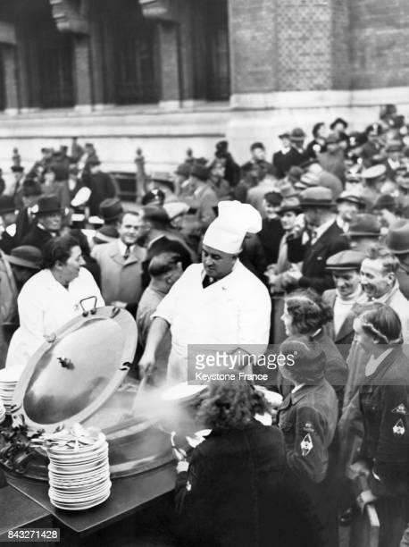 Un cuisinier plonge sa louche dans un chaudron géant pour servir les Berlinois lors du dimanche du ragoût sur la place de l'Hôtel de Ville le 10...
