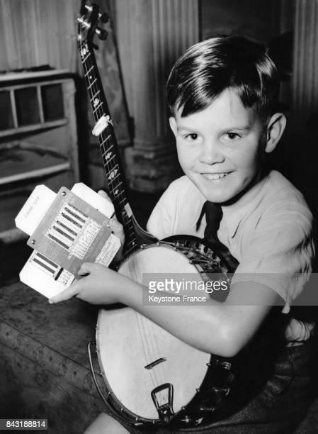 Un enfant de huit ans muni d'un banjo présente la 'meloda music slide' système mis au point par son père Mr Miles pour faire apparaître en un seul...