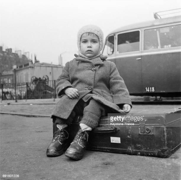 Un enfant est assis sur une valise en attendant le départ en vacances à Paris France le 3 avril 1953
