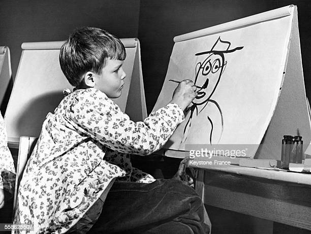 Un enfant membre du club 'Paint Orchestra' peint sur une grande feuille de papier le 21 octobre 1945 aux EtatsUnis