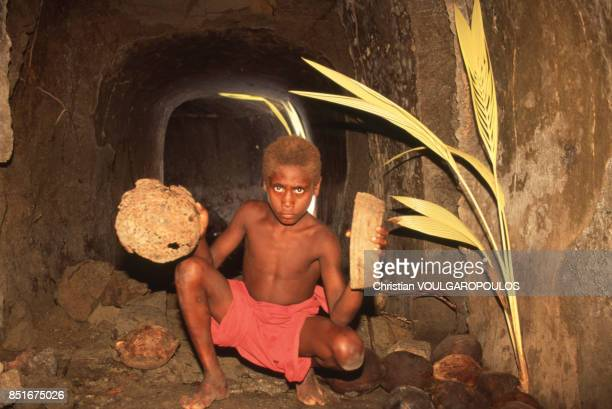Un enfant montre un casque et un chargeur japonais trouvés dans un tunnel près de Rabaul PapouasieNouvelleGuinée en juin 1991